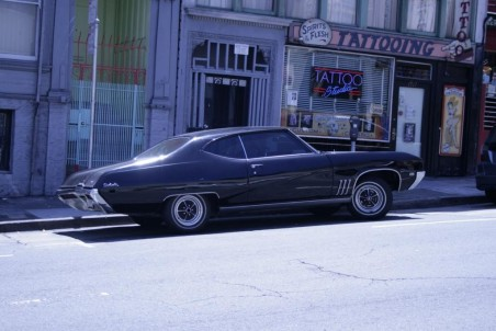 A typical San Francisco scene - Chevy Impala parked outside a tattoo parlour